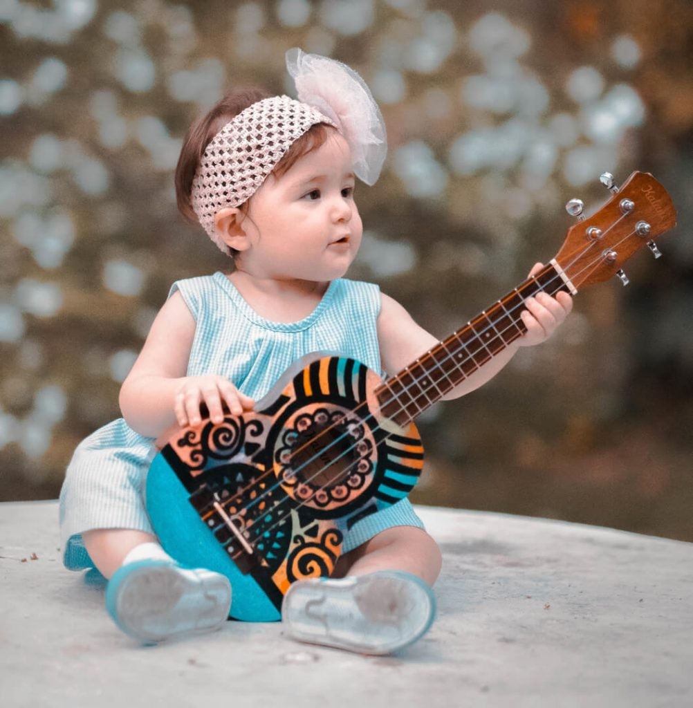 Baby plays a ukulele which may be easier than guitar