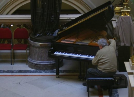 Piano tuning costs - image of technician tuning a Grand Piano