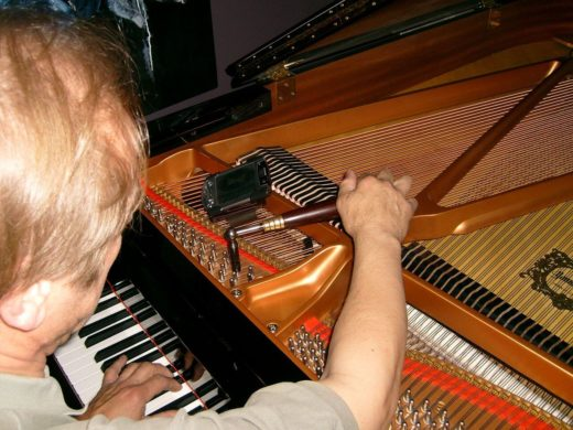 Tuning your own piano - a man tuning a grand piano