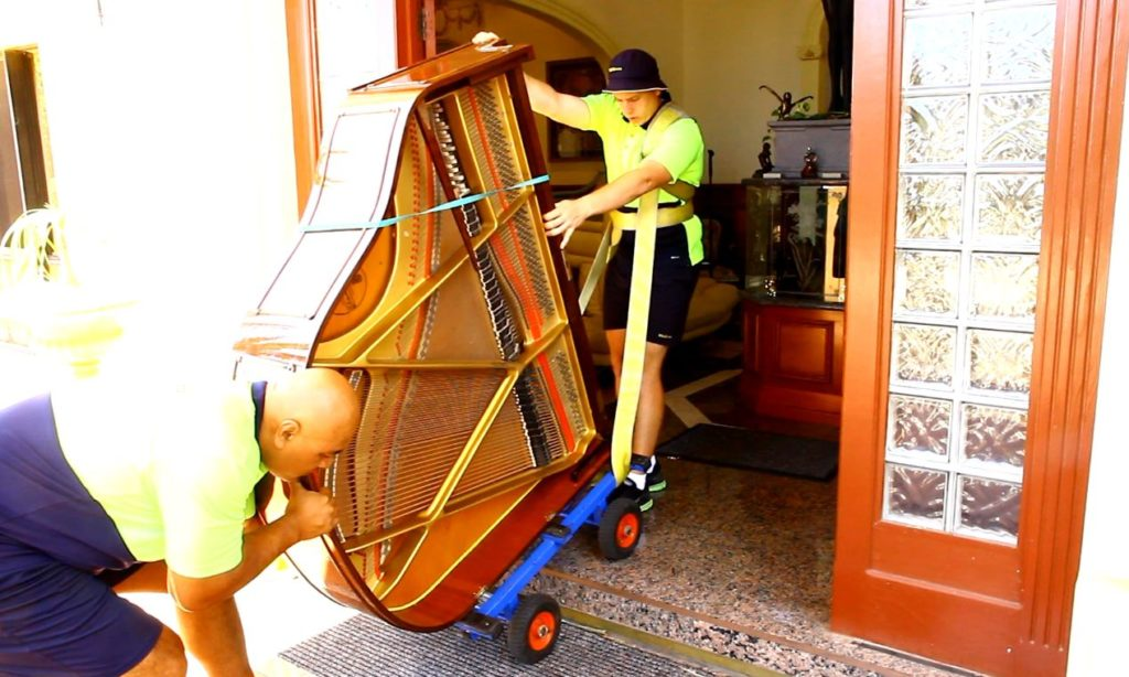 Movers move a piano up a step (which increases the cost)