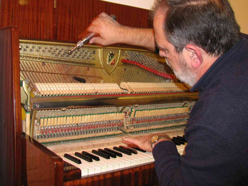 piano tuner tuning piano (after a piano is restrung)
